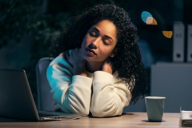 Schot van vermoeide afrikaanse jonge vrouw met nekpijn die met laptop werkt terwijl ze ontspant van het werk op kantoor thuis.