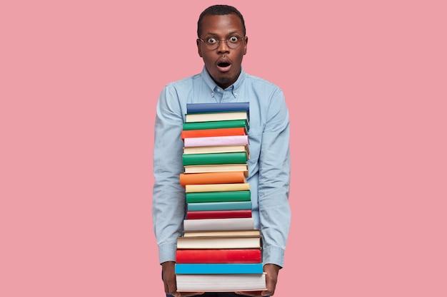 Schot van verrast afro-amerikaanse man draagt stapel kleurrijke boeken, bang voor deadline, gekleed in formele kleding, houdt mond open