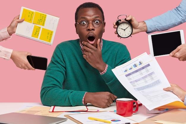 Schot van verrast bang zwarte man kijkt met angstige uitdrukking, draagt een ronde bril, bestudeert documenten met afbeeldingen en grafieken