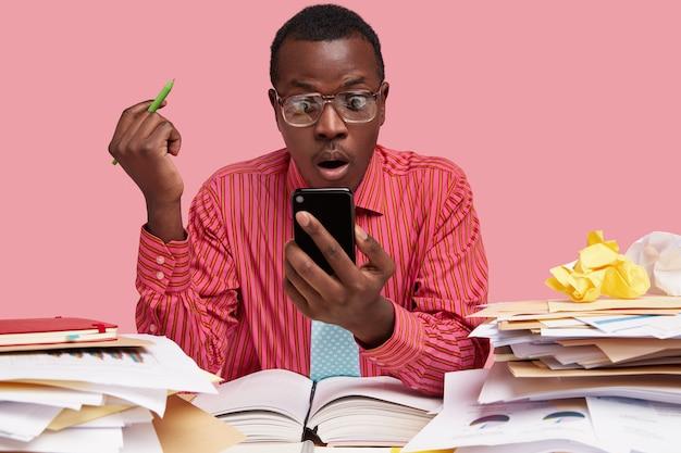 Schot van verrast donkere huid man gekleed in roze formele shirt, houdt mobiele telefoon, leest melding, heeft gezichtsuitdrukking verbijsterd