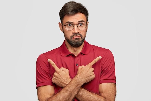 Schot van verwarde onwetende man met baard en snor, wijst met wijsvingers in verschillende richtingen, heeft een onbewuste uitdrukking, verbaasde blik, poseert tegen een witte muur, gebaren