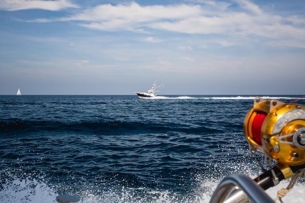 Schot van vissersboten die op de oceaangolven varen onder de blauwe hemel