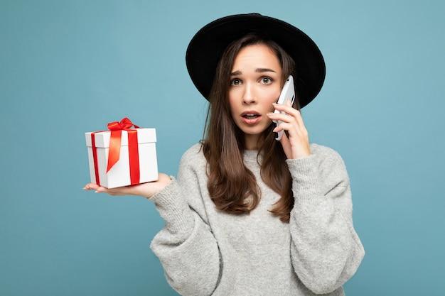 Schot van vrij triest geschokt jonge brunette vrouw geïsoleerd over blauwe muur muur stijlvol dragen