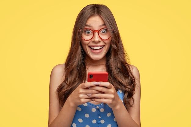 Schot van vrolijk vrouwelijk model draagt een bril, houdt mobiele telefoon vast, maakt foto's, praat via videoboodschap, heeft leuke vriendelijke praat, gekleed in modieuze outfit, geïsoleerd over gele muur