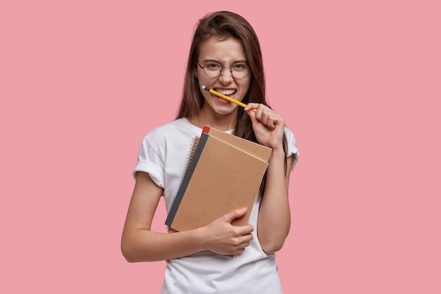 Schot van vrolijke blanke vrouw bijt potlood, draagt spiraalvormige notitieboekjes, schrijft notities, heeft donker steil haar, draagt casual t-shirt, geïsoleerd over roze muur