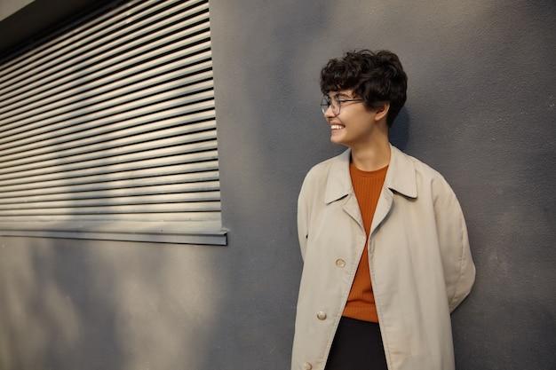 Schot van vrolijke jonge krullende brunette vrouw met kort kapsel handen achter achter houden en gelukkig opzij kijken met charmante glimlach, beige trenchcoat en foxy trui dragen terwijl poseren buiten