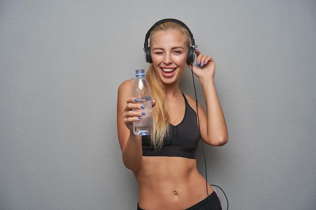 Schot van vrolijke slanke blonde vrouw met lang haar, luisteren naar muziek in haar oortelefoons en fles water in opgeheven hand houden, vrolijk knipogen naar de camera terwijl ze over de lichtgrijze achtergrond staat