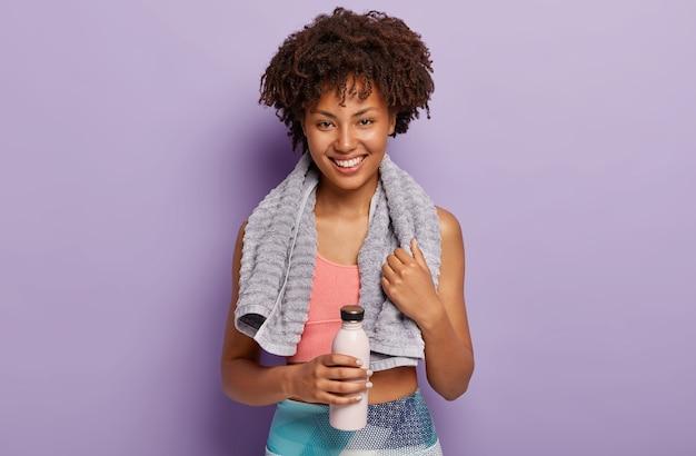 Schot van vrolijke vrouwelijke atleet neemt pauze, staat binnen met flessen water