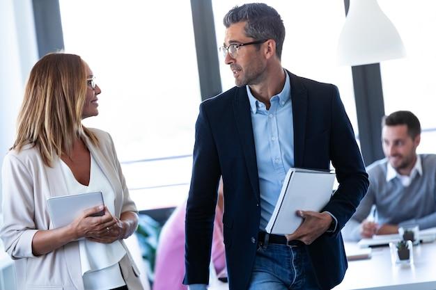 Schot van vrouw en zakenman praten over de vergadering terwijl ze het kantoor verlaten.