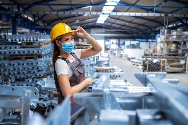 Schot van vrouw fabrieksarbeider in uniform en veiligheidshelm dragen gezichtsmasker in industriële productie-installatie