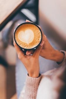 Schot van vrouw handen houden kopje warme koffie met hart ontwerp gemaakt van schuim.