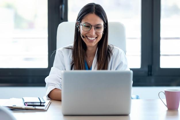 Schot van vrouwelijke arts die met collega's praat via een videogesprek met een laptop in het overleg.