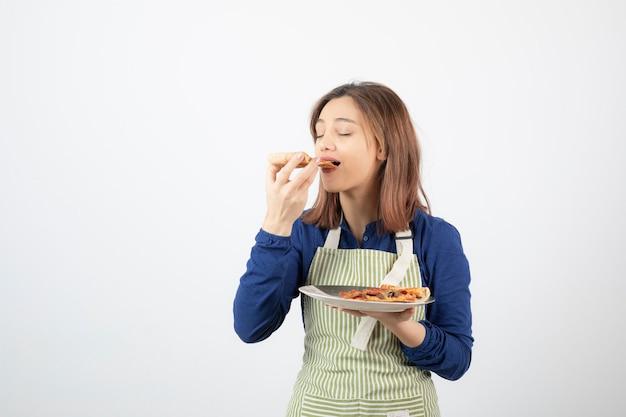 Schot van vrouwelijke kok in schort die stuk pizza op wit eet