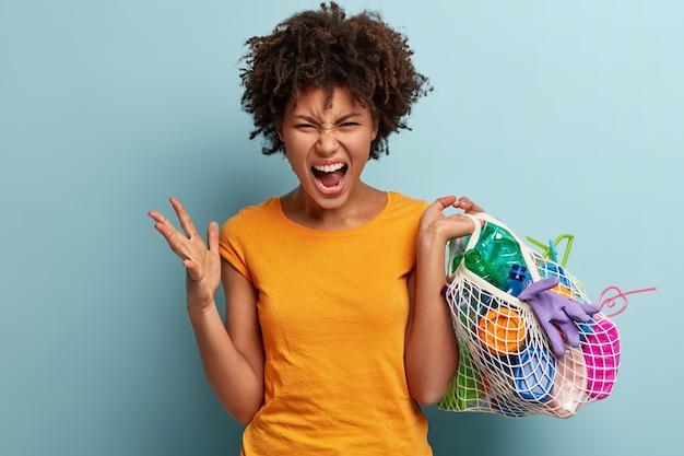 Schot van wanhopige boze jonge vrouw gebaren boos, draagt plastic voorwerp in netzak, geïrriteerd door besmetting, draagt oranje t-shirt, staat tegen blauwe muur. plastic bewustzijn concept