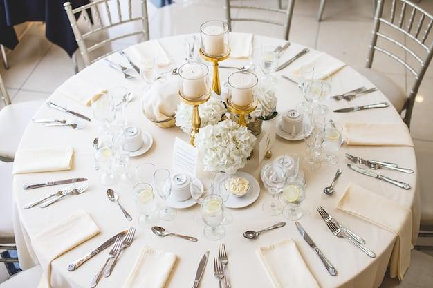 Schot van witte bloemboeketten en pijlerkaarsen in gouden kandelaar op een huwelijkstafel