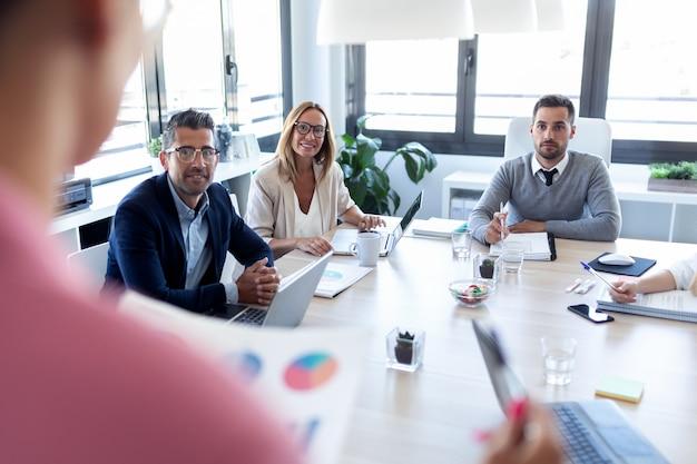 Schot van zakenmensen die aantekeningen maken met een laptop en opletten tijdens een conferentie over een coworking-plek.