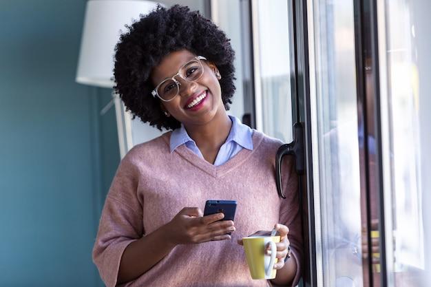 Schot van zakenvrouw die naar de camera kijkt terwijl ze haar mobiele telefoon gebruikt en naast het raam op kantoor staat.