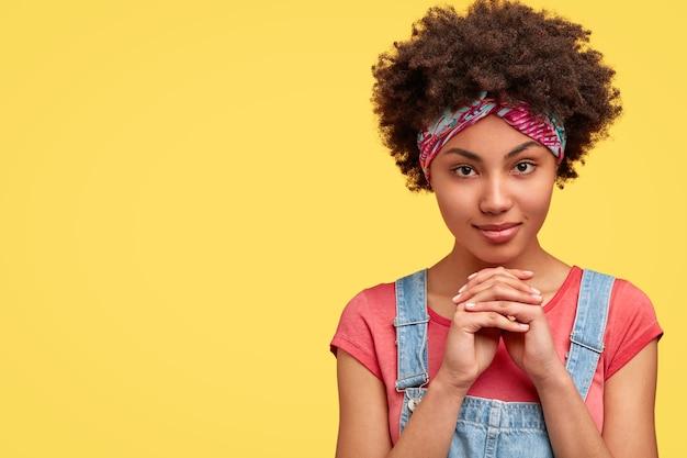 Schot van zelfverzekerde afro-amerikaanse vrouw houdt de handen bij elkaar onder de kin, kijkt serieus direct, denkt ergens aan, staat tegen gele muur met kopie ruimte