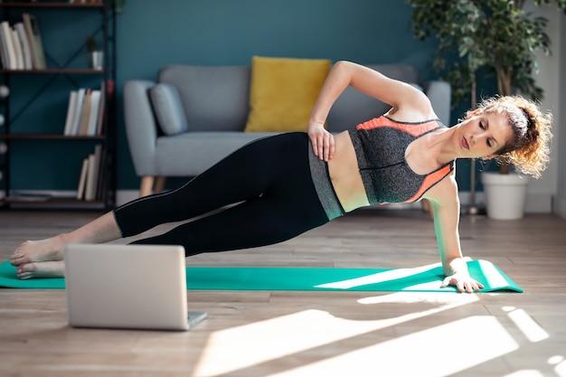 Schot van zelfverzekerde sportieve jonge vrouw die hypopressieve oefeningen doet na online gymlessen via laptop op de vloer in haar woonkamer thuis.