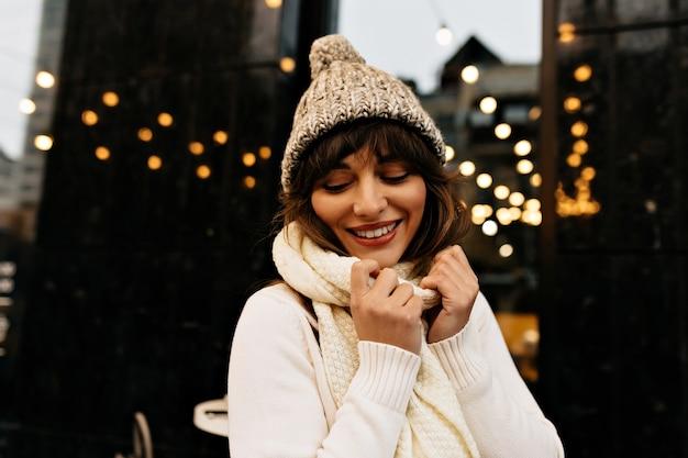 Schot van zorgeloze vrouw met lang bruin haar en charmante glimlach.