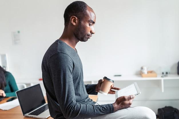 Schot van zwarte jonge zakenman die met digitale tablet werkt terwijl hij koffie drinkt op kantoor.