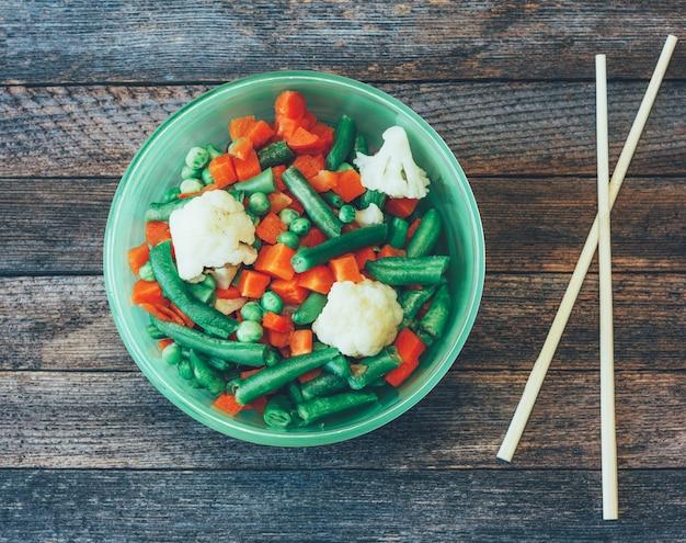 Schotel aziatische keuken gemengde groenten en eetstokjes op de oude houten tafel