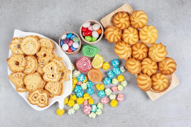 Schotel en dienblad vol koekjes met een bosje snoepjes en marmelades in het midden op marmeren achtergrond. hoge kwaliteit foto