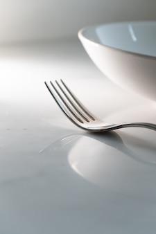 Schotel en vork op witte marmeren textuurachtergrond. concept voor eet- en eetservies