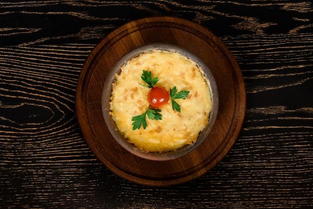 Schotel gebakken met kaas, versierd met cherrytomaat en peterselie in een kleiplaat op een houten bord op een donkere houten tafel.