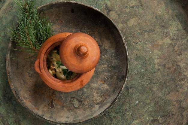 Schotel in een aarden pot op een oud antiek dienblad