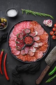 Schotel met gezouten vlees van traditionele spaanse tapas. chorizo, salchichon, longaniza en fuet op zwart gestructureerd oppervlak, bovenaanzicht.