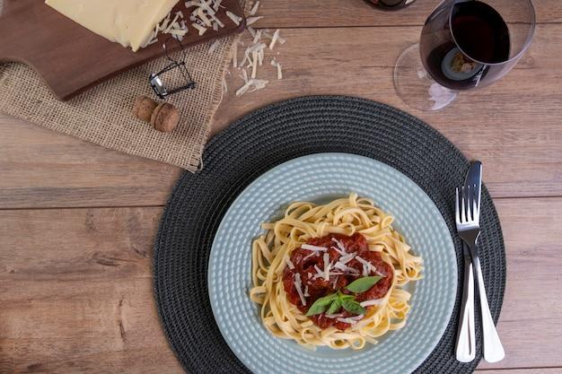 Schotel met noedels gegarneerd met tomatensaus, met een glas mousserende rode wijn.