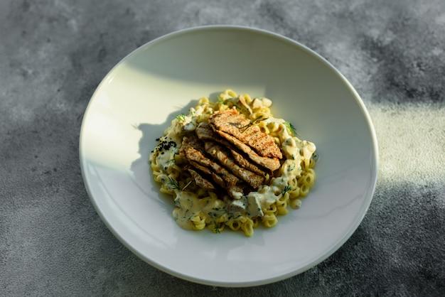 Schotel met stukjes vlees, pasta, groenten, saus van een foie gras en de olijfaarde
