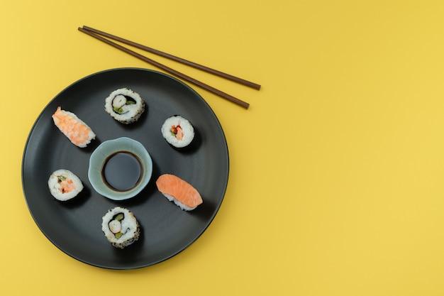 Schotel met sushi en eetstokjes op een gele tafel. voedsel concept.
