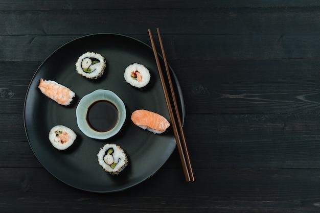Schotel met sushi en eetstokjes op een zwarte houten achtergrond. kopieer ruimte. voedsel concept.
