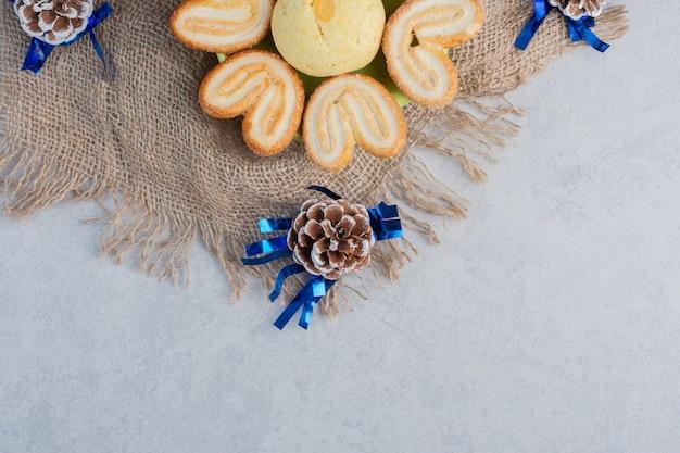 Schotel met verrukkelijke koekjes op een stuk stof te midden van dennenappels op een marmeren oppervlak