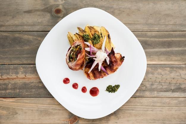 Schotel met vlees en aardappel op houten bureau
