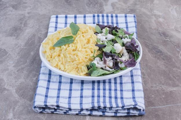 Schotel rijstpilau vergezeld van een salademengsel van amarant, basilicum en bloemkool op een opgevouwen handdoek op een marmeren ondergrond