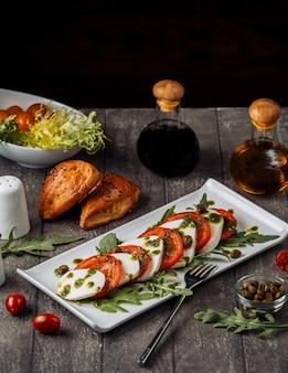 Schotel van carpese salade gegarneerd met basilicumbladeren en olijven