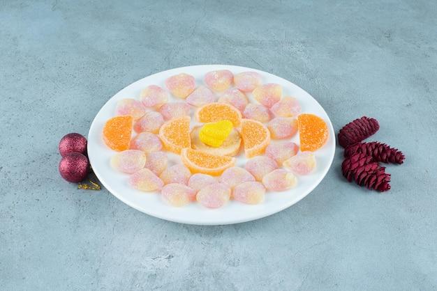 Schotel van diverse marmelades, met dennenappels en kerstballen op marmer.