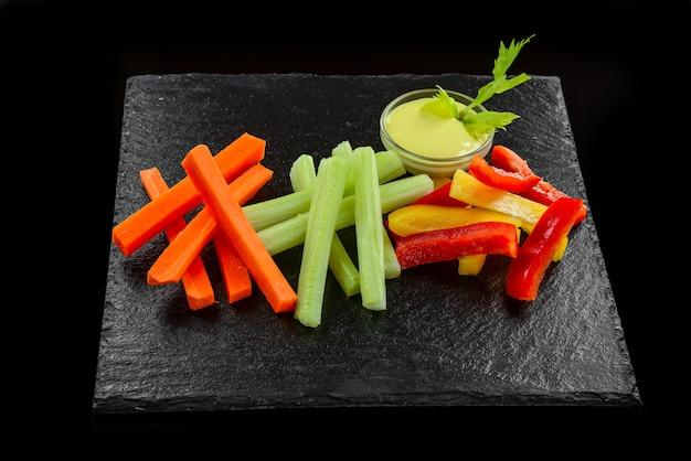 Schotel van diverse verse groenten met yoghurtdip, op een zwarte achtergrond