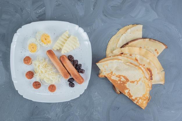 Schotel van eieren, kaas, olijven en worstjes naast pannenkoeken op marmeren tafel.