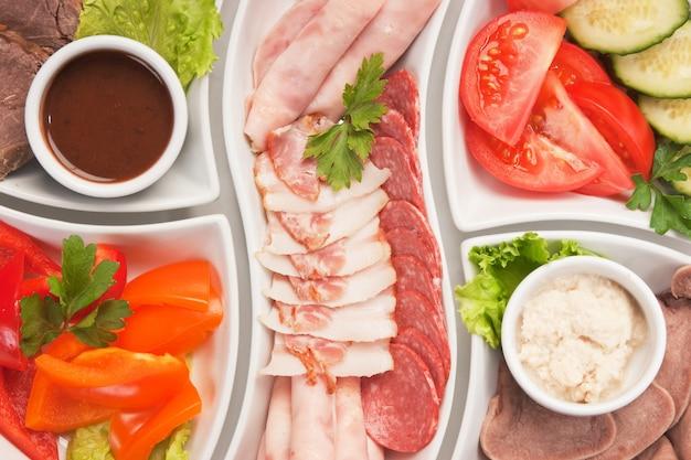 Schotel van geassorteerde worsten en groenten