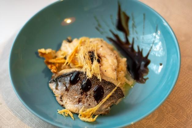 Schotel van gebakken vis en parmezaanse chips op een blauw bord