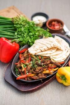 Schotel van gefrituurde dunne plakjes lamsvlees gekookt met kleurrijke paprika