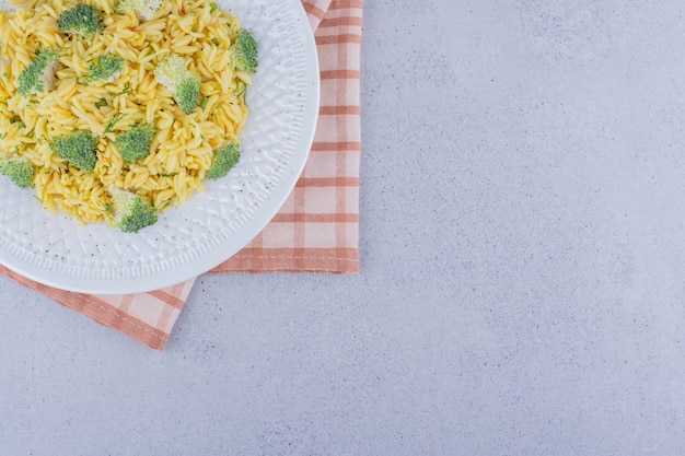 Schotel van gekookte bruine rijst met broccolibovenste laagje op marmeren achtergrond.