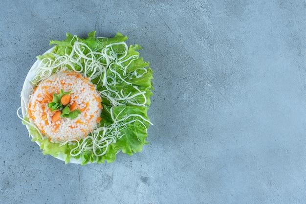 Schotel van gekookte rijst versierd met kaas en sla op marmer.
