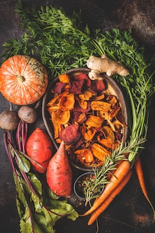 Schotel van gezonde plantaardige chips van bieten, zoete aardappelen, pompoen en wortelen met ingrediënten op donkere tafel.