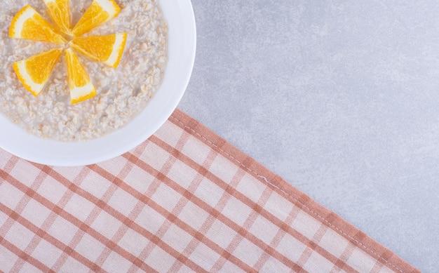 Schotel van havermout gegarneerd met stukjes sinaasappel op marmeren oppervlak