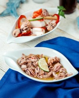 Schotel van inktvissen gegarneerd met citroen geserveerd op witte tafel